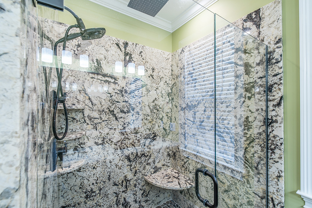 Luxurious walk-in shower with Delicatus White Granite walls, shelves, corner bench square raincan shower head and glass door