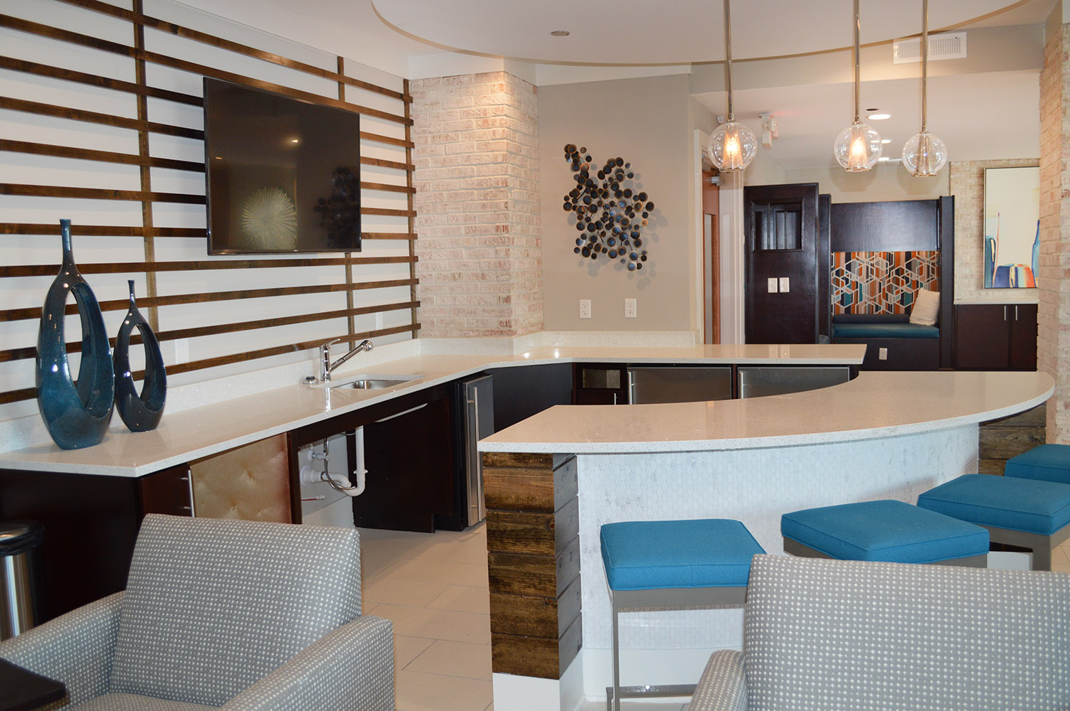 Comfortable commons area featuring White quartz countertops and tile bar front by East Coast Granite