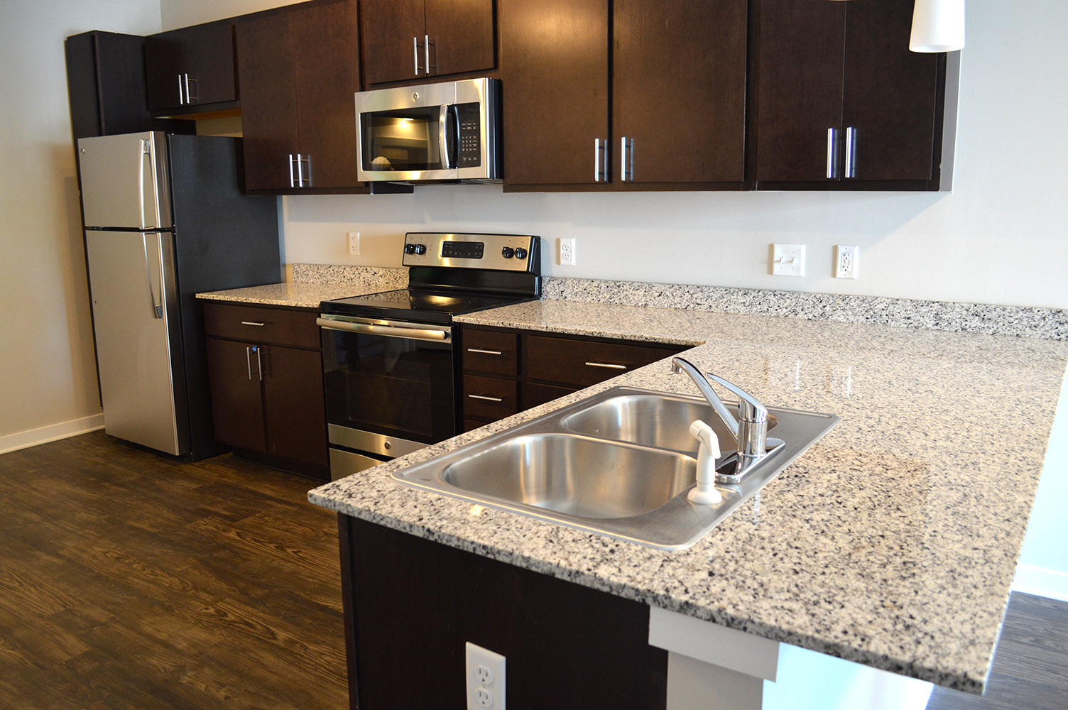 Large granite kitchen countertops really set a luxurious upscale vibe in the Main & Stone apartments