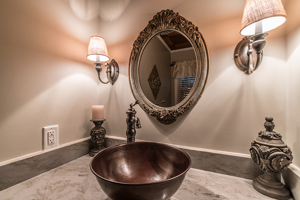A vanity with a classic feel.  Sea Pearl Quartzite makes the top and backsplash with copper vessel and accented faucet