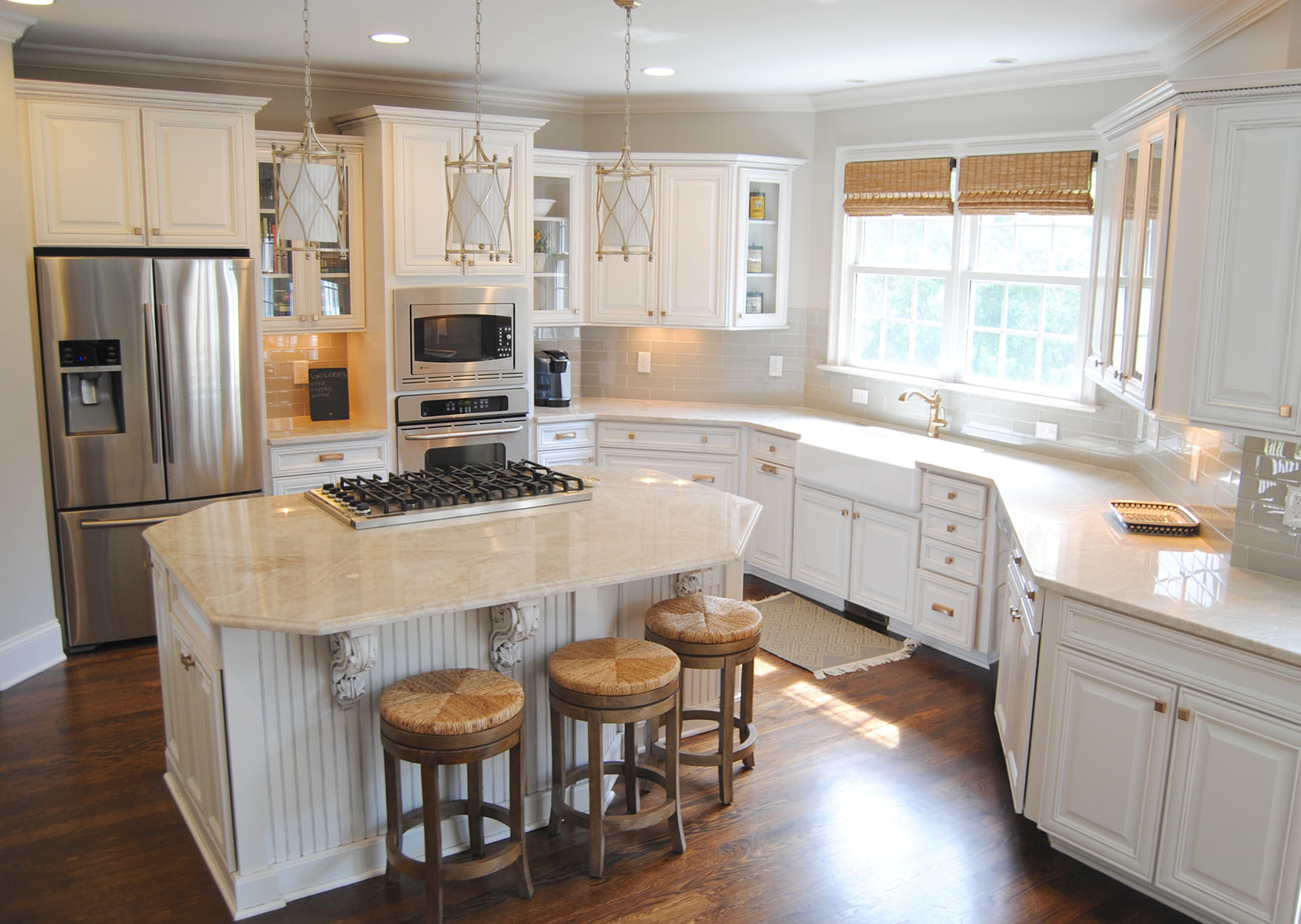 Taj Mahal Quartzite ties the whites and grays from the subway tiles and cabinets together.  Stainless appliances and dark hardwoods bring beautiful contrast to the room.