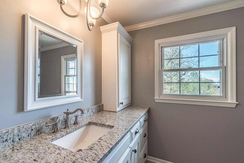Verona granite vanity top in a Gray bathroom with white shaker cabinets