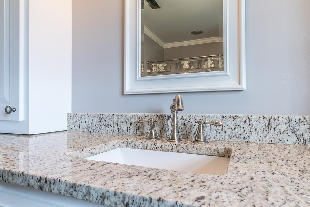 Verona granite vanity top with white shaker cabinets and matching mirror